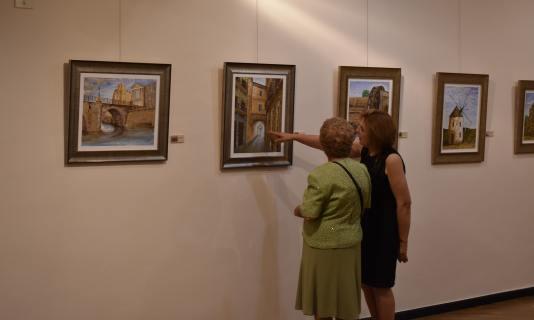 13 seguidores del artista observando las obras del pintor