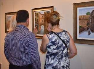 14 seguidores del artista observando las obras del pintor